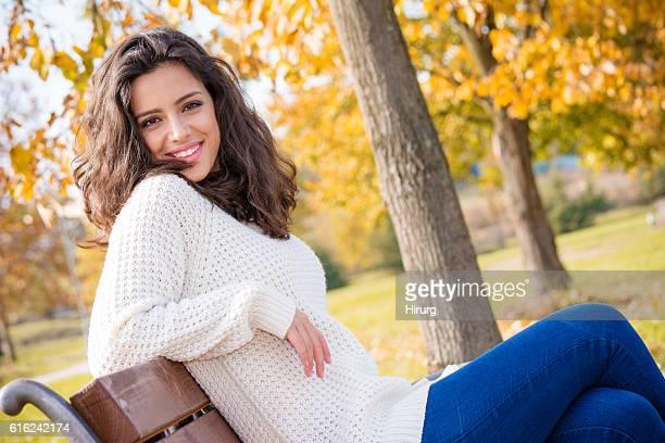 Beautiful teenage girl sitting in the park