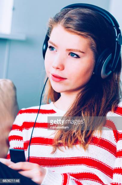 Beautiful teenage girl streams a podcast and listens to the content