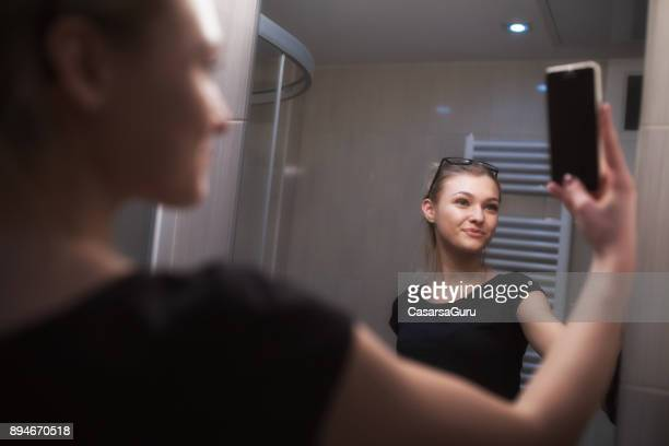 Beautiful Teenage Girl Taking a Selfie in Bathroom