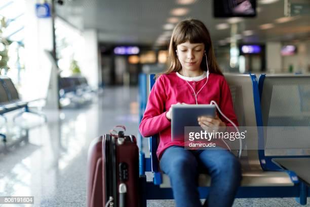 Beautiful teenage girl waiting for departure at airport