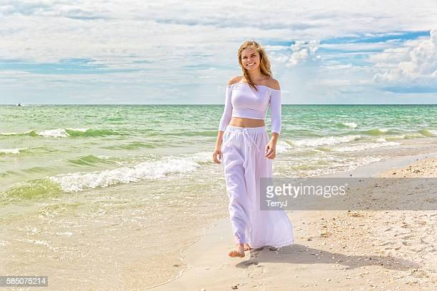 Beautiful Teenage Girl Walks Along the Beach