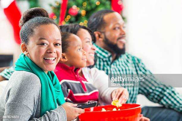 Beautiful teenage girl watches movie with family at Christmastime