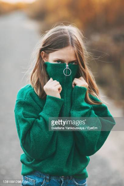 beautiful teenage girl with blonde hair and blue eyes in a warm green sweater in an autumn park. - green coat stock pictures, royalty-free photos & images