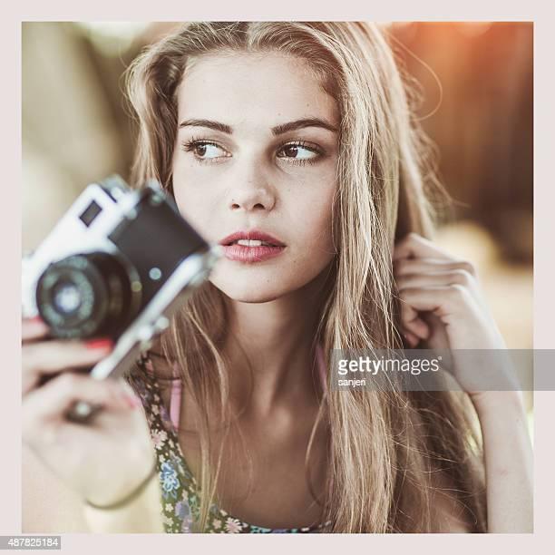 Belle jeune femme avec caméra rétro