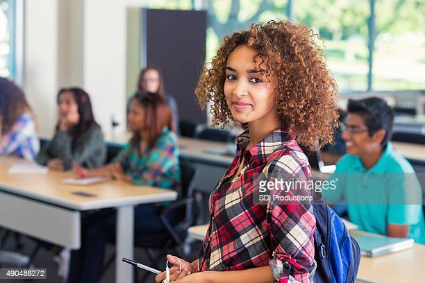 Beautiful teenage high school student smiling before class
