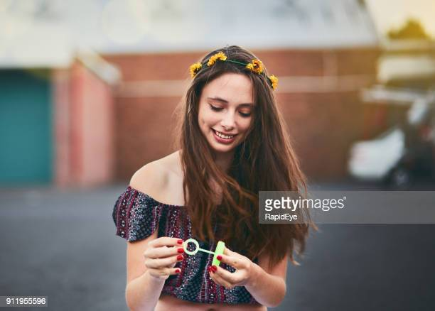 beautiful teenager blowing bubbles outside holds bubble wand, smiling - off shoulder stock pictures, royalty-free photos & images