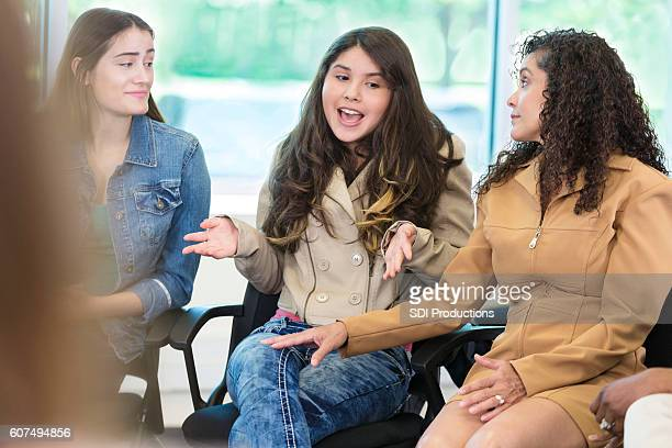 Beautiful teenager makes a point during discussion group