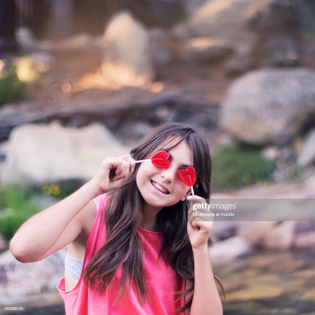 Beautiful teenager with heart-shaped lollipops : Stock Photo