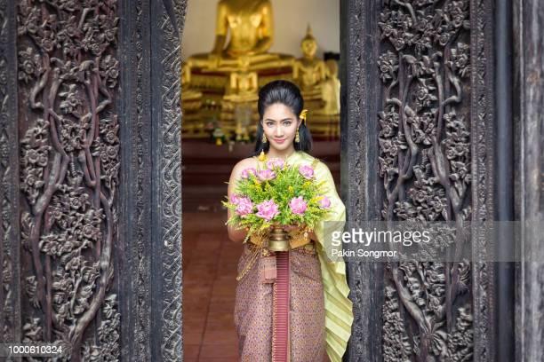 beautiful thai girls in thai traditional costume hand holding lotus flower and standing near old door at temple in thailand - prayer pose greeting bildbanksfoton och bilder