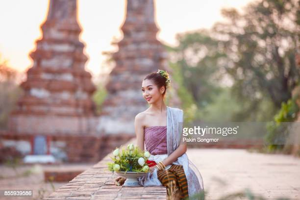 Beautiful Thai girls in thai traditional costume trying to roll up lotus flower at sunset time