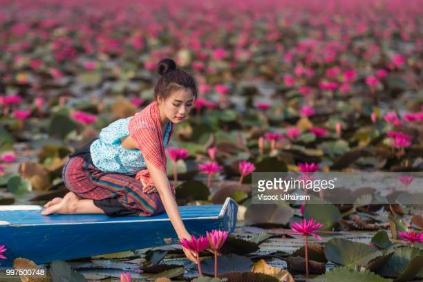 beautiful thai lady in thai dress sitting on boat is holding lotus in the river. - water lily stock photos and pictures