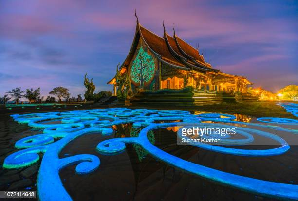 beautiful thai temple and sky after sunset from the luminescent paint with reflection on water at sirindhorn wararam temple (wat phu prao). - phosphorescence stock pictures, royalty-free photos & images