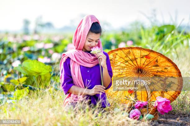 fe81c6ee5 Beautiful thai women farmer wearing thai traditional dress and walk on the  lotus lake and looking