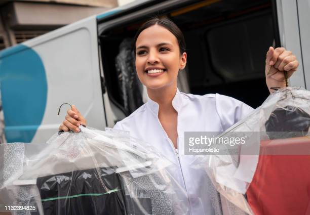 beautiful thoughtful woman looking away while delivering dry cleaned clothes - dry cleaned stock pictures, royalty-free photos & images