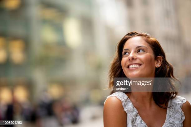 hermosa mujer pensativa sonriendo al aire libre - mirar hacia arriba fotografías e imágenes de stock