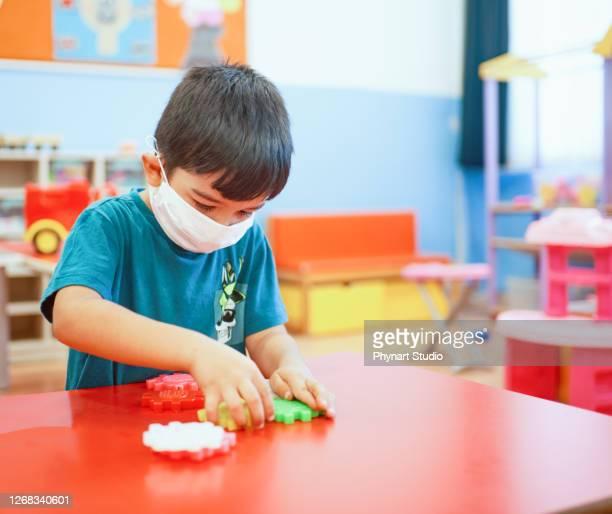 幼稚園で建設ブロックで遊ぶ美しい幼児の少年 - 南ヨーロッパ民族 ストックフォトと画像