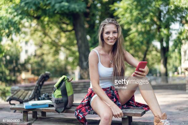 Beautiful tourist woman texting on her mobile phone in the city park