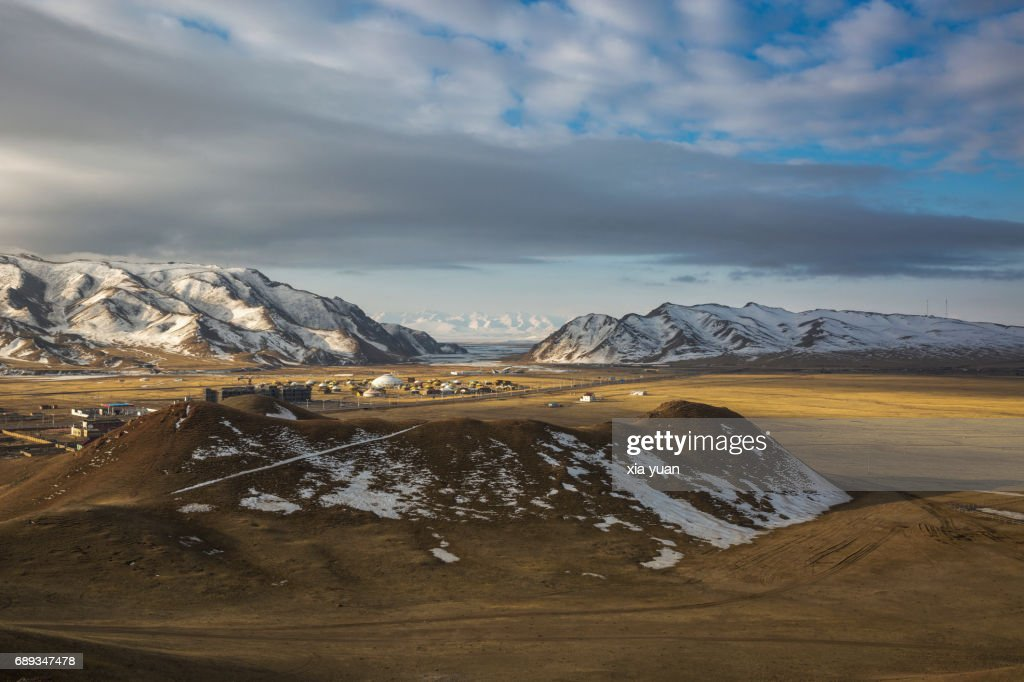 Beautiful town on prairie admist snowcapped mountain,Bayanbulak,China : Stock Photo