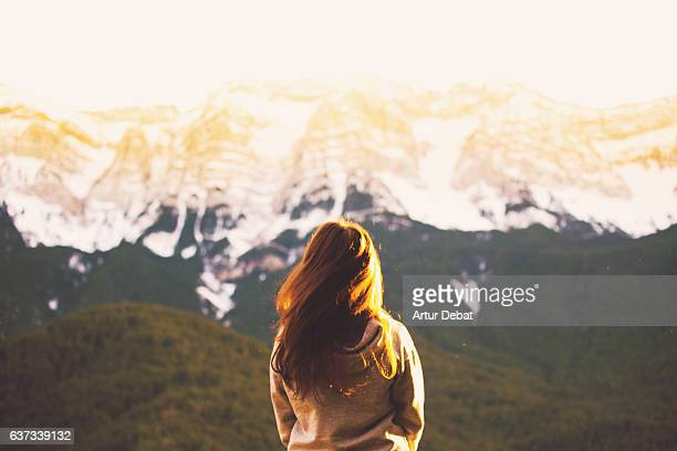 Beautiful traveler girl swing her hair in the Catalan Pyrenees during winter contemplating nice snowy mountain range during sunset light.