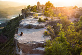 Beautiful traveler woman contemplating the view from the stunning Siurana town on top of cliff with amazing views during travel vacations in the Catalonia region.