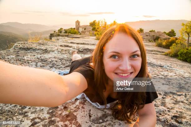 Beautiful traveler woman taking a selfie laying with smiling face on the top of the stunning Siurana town with amazing views from cliff during travel vacations in the Catalonia region.