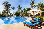 Beautiful tropical beach front hotel resort with swimming pool, sunshine