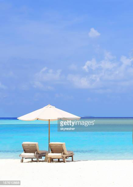 Beautiful tropical beach with deck chairs and parasol.