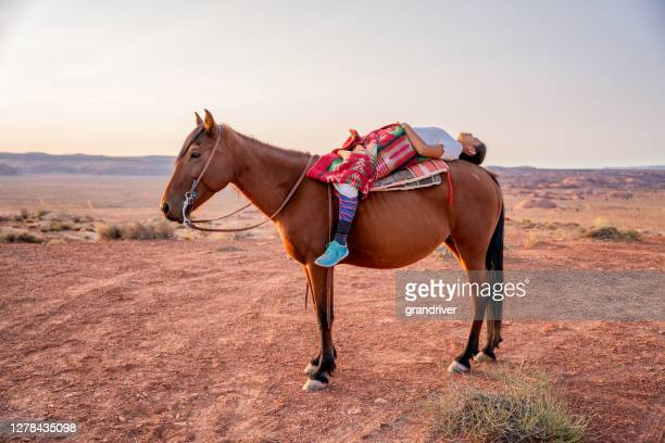 beautiful twelve year old navajo girl lying on the back of her pet bay quarter horse in the desert near the  monument valley tribal park in northern arizona - apache stock pictures, royalty-free photos & images