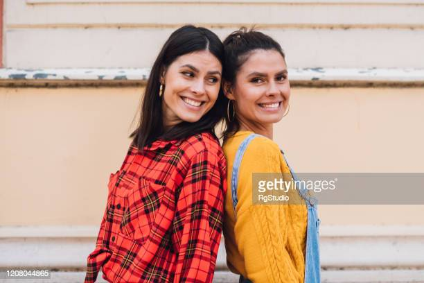 beautiful twin sisters posing outdoors - sister stock pictures, royalty-free photos & images