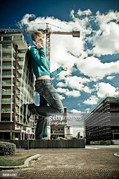 beautiful urban giant girl talking by mobile phone - giantess stock photos and pictures