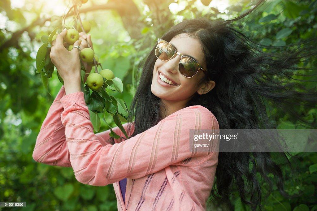 Beautiful urban girl holding tree branch full of Asian pear. : Stock Photo