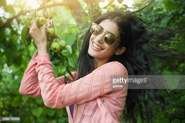 Beautiful urban girl holding tree branch full of Asian pear.