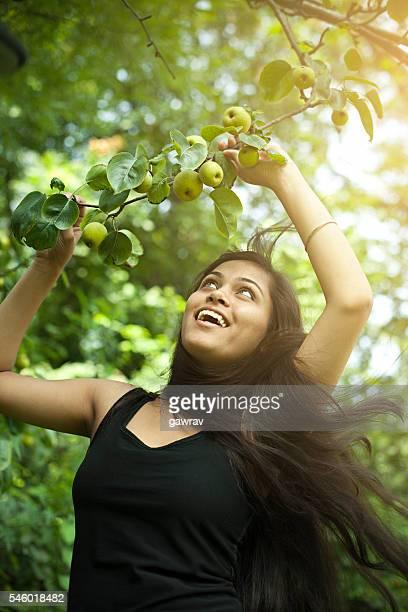 Beautiful urban girl holding tree branch full of Asian pear.