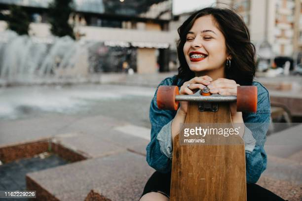 beautiful urban young female in the city with her longboard. - brace stock pictures, royalty-free photos & images