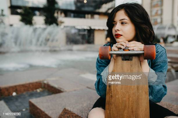 Beautiful Urban young female in the city with her longboard.