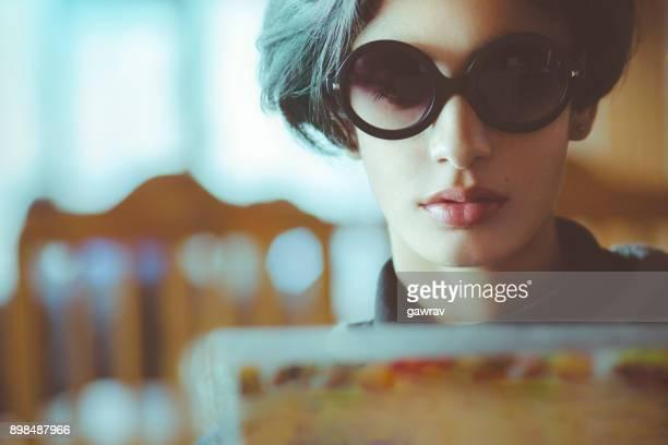 Beautiful urban young woman reading menu card.