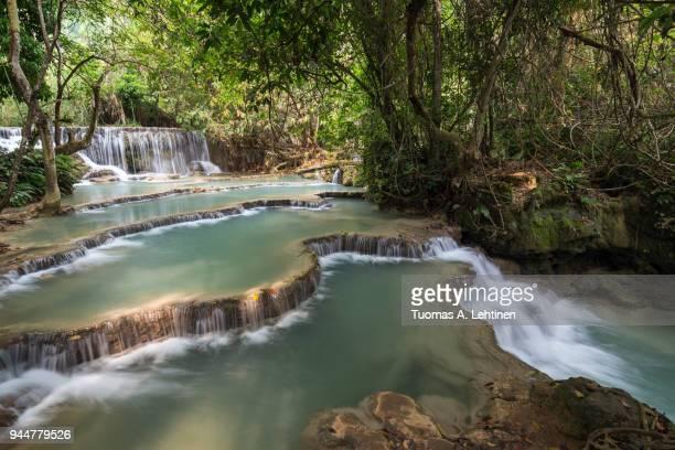 Beautiful view of a small waterfall and cascades at the Tat Kuang Si Waterfalls near Luang Prabang in Laos on a sunny day.