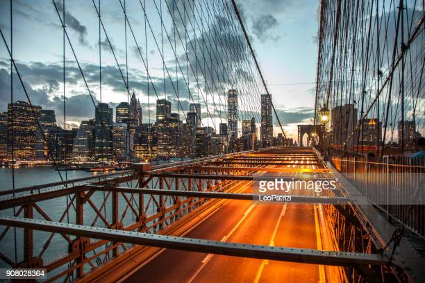 beautiful view of lower manhattan in new york at dusk - suspension bridge stock photos and pictures