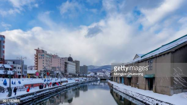 beautiful view of old warehouse at otaru canal in sapporo, hokkaido, japan with snow cover on roof. traveler traveling at otaru canal is one of most famous place in sapporo, hokkaido, japan in winter - 小樽市 ストックフォトと画像