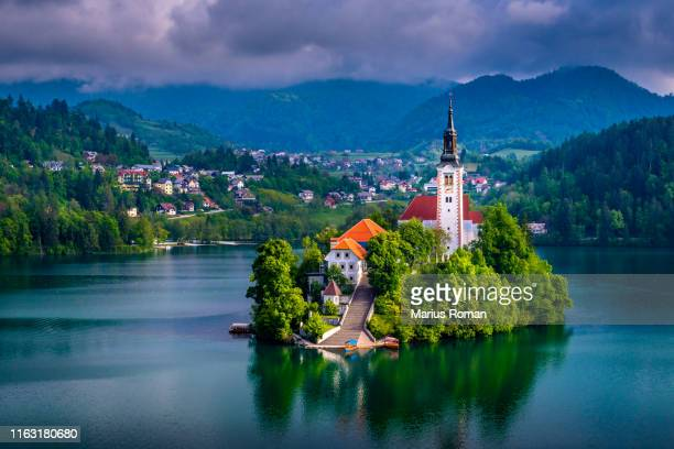 beautiful view of pilgrimage church of the assumption of maria, famous bled island (blejski otok), and scenic bled lake, with julian alps in the background, slovenia, europe. - slovenia stock pictures, royalty-free photos & images
