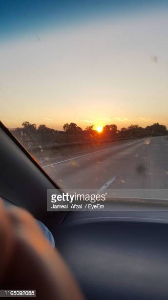 beautiful view of sunset seen through car windshield - tetbury stock pictures, royalty-free photos & images
