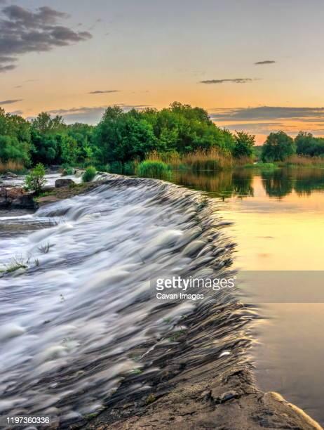 beautiful view of the dam on the river at sunset - dique barragem imagens e fotografias de stock