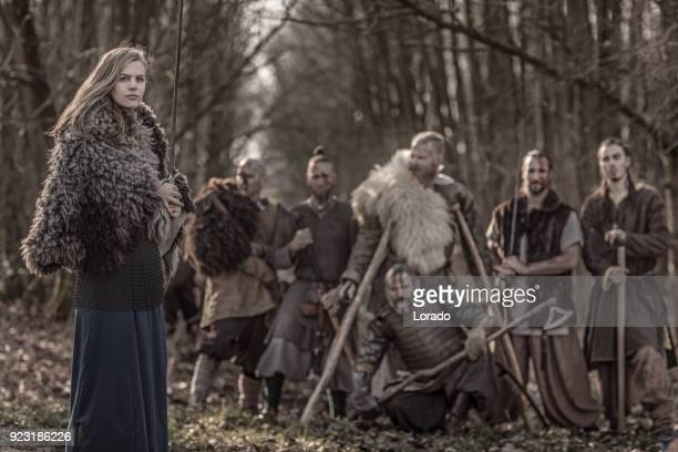 beautiful viking warrior royal female with her army on a winter battlefield forest - medium group of people stock pictures, royalty-free photos & images