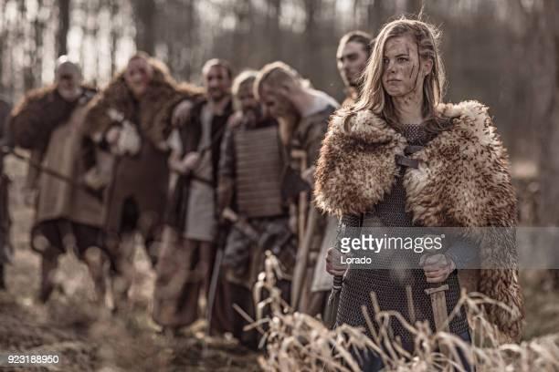schönen wikinger krieger königliche frau mit ihrer armee auf einem schlachtfeld winterwald - wikinger stock-fotos und bilder