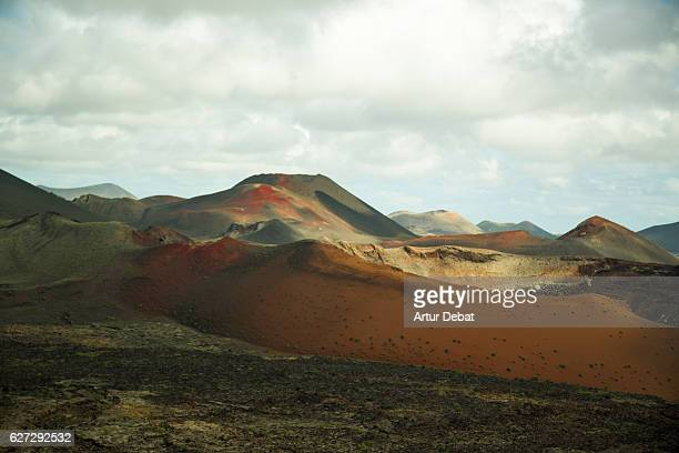 Beautiful volcanic landscape in the national park of Timanfaya in the Lanzarote island with nice red colors and other planet view.