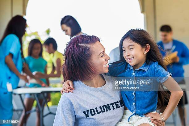 Beautiful volunteer and adorable little girl smile at each other