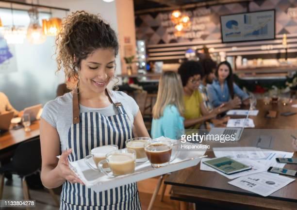 empregada de mesa bonita em um escritório coworking que prende uma bandeja com latte e café para clientes no fundo - garçonete - fotografias e filmes do acervo