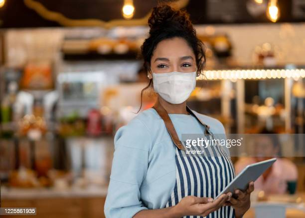 beautiful waitress working at a restaurant wearing a facemask - restaurant stock pictures, royalty-free photos & images