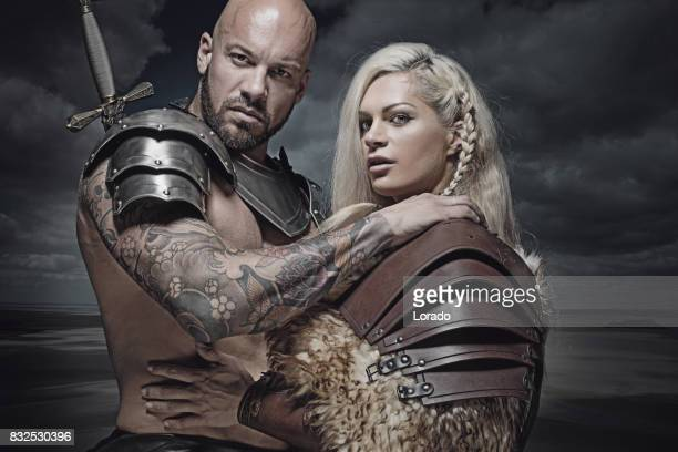 Beautiful weapon wielding viking warrior couple in emotional pose