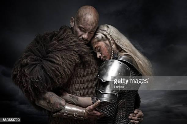 Beautiful weapon wielding viking warrior couple in emotional pose